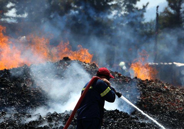 Πυροσβέστης επιχειρεί για την κατάσβεση πυρκαγιάς στο Μενίδι, 19 Ιουλίου 2018