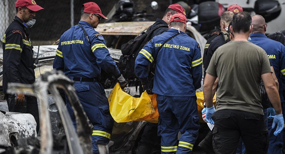Πυροσβέστες μεταφέρουν τη σορό ενός νεκρού από την πυρκαγιά