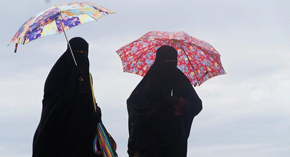 Γυναίκες φορούν νικάμπ και κρατούν ομπρέλες