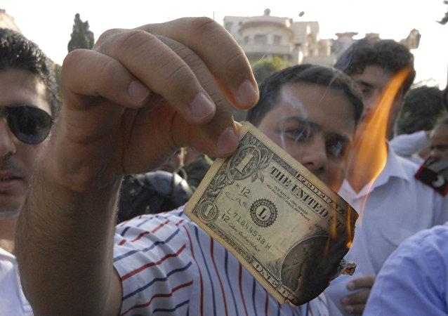 Διαδηλωτής στη Συρία καίει χαρτονόμισμα δολαρίου