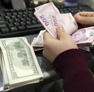 Γυναίκα μετρά αμερικανικά δολάρια και τουρκικές λίρες σε ανταλλακτήριο νομισμάτων στην Κωνσταντινούπολη